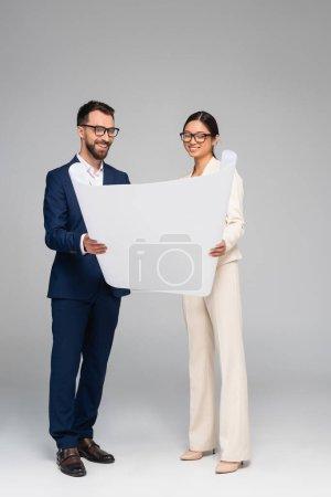Photo pour Vue complète du couple interracial d'hommes d'affaires regardant le papier blanc sur gris - image libre de droit