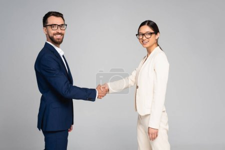 Photo pour Couple of interracial business partners shaking hands while looking at camera isolated on grey - image libre de droit