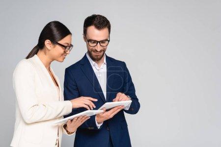 Photo pour Couple interracial de collègues d'affaires en blazers et lunettes à l'aide de tablettes numériques isolées sur gris - image libre de droit