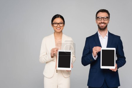 Photo pour Interracial couple of business partners in eyeglasses showing digital tablets with blank screen isolated on grey - image libre de droit