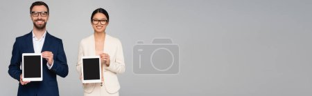 Photo pour Récolte panoramique de couple interracial d'hommes d'affaires montrant des tablettes numériques avec écran blanc isolé sur gris - image libre de droit