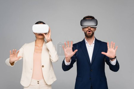 excited businesspeople in vr headsets gesturing like touching something isolated on grey
