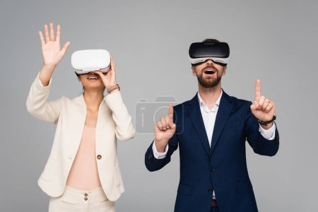 Photo for Excited business partners in vr headsets gesturing like touching something isolated on grey - Royalty Free Image
