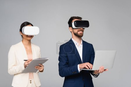 businesswoman holding folder and pen while using vr headsets together with businessman typing on laptop isolated on grey