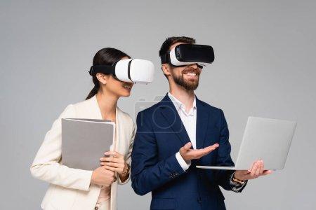 Photo pour Homme d'affaires pointant vers ordinateur portable tout en utilisant des casques vr avec partenaire d'affaires isolé sur gris - image libre de droit