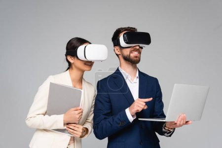 Photo for Businesswoman holding folder while using vr headsets together with colleague pointing with finger at laptop isolated on grey - Royalty Free Image