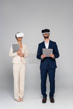 Photo pour Vue pleine longueur des hommes d'affaires en costumes et casques vr tenant des documents tout en se tenant sur gris - image libre de droit