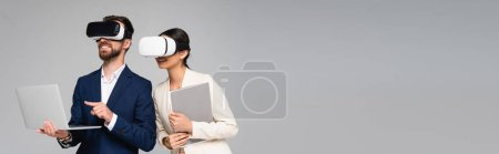 horizontal image of businessman pointing with finger at laptop while using vr headsets together with colleague isolated on grey