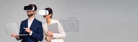 Photo pour Image horizontale de l'homme d'affaires pointant du doigt vers un ordinateur portable tout en utilisant des casques vr avec un collègue isolé sur gris - image libre de droit