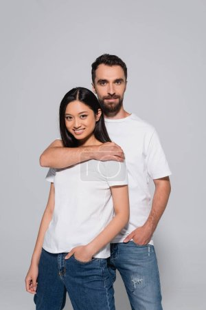 Photo for Bearded man hugging brunette asian woman while posing with hands in pockets isolated on grey - Royalty Free Image