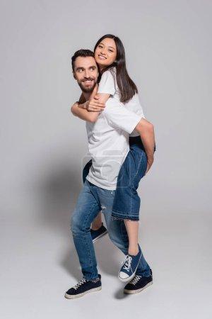 Photo for Bearded man in white t-shirt and jeans piggybacking asian girlfriend on grey - Royalty Free Image
