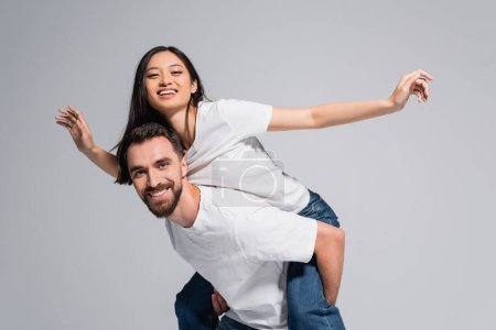 Photo for Young man in white t-shirt piggybacking excited asian girlfriend imitating flying isolated on grey - Royalty Free Image