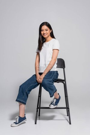 brunette asian woman in jeans, gumshoes and white t-shirt sitting on chair and looking at camera on grey