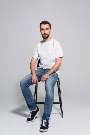 Photo for Bearded, young man in jeans and white t-shirt looking at camera while sitting on chair on grey - Royalty Free Image
