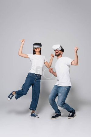 young, excited couple in vr headsets, jeans and white t-shirts dancing on grey