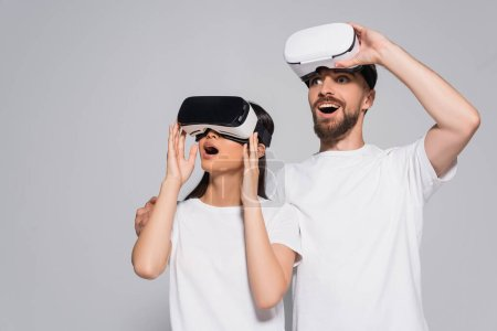 excited woman using vr headset near bearded man looking away isolated on grey