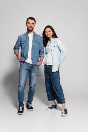 Photo for Full length view of stylish interracial couple in jeans and denim shirts looking at camera on white - Royalty Free Image