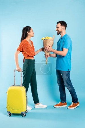 man in polo t-shirt and jeans presenting bouquet to asian woman with yellow suitcase on blue