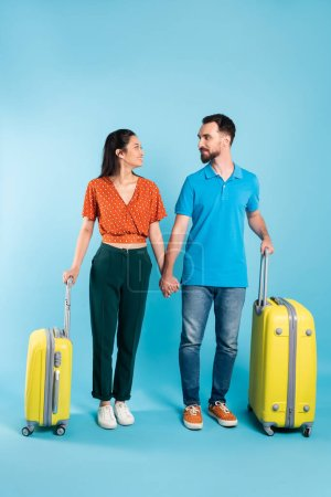 young interracial couple looking at each other and holding hands while standing with travel bags on blue
