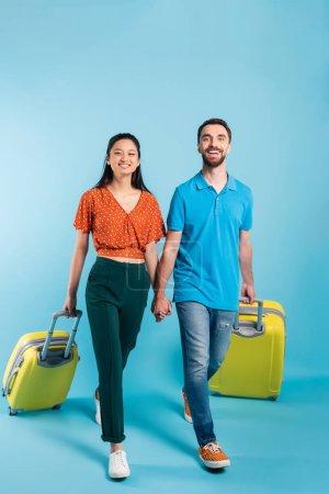 Foto de Full length view of interracial couple of tourists holding hands while walking with suitcases on blue - Imagen libre de derechos