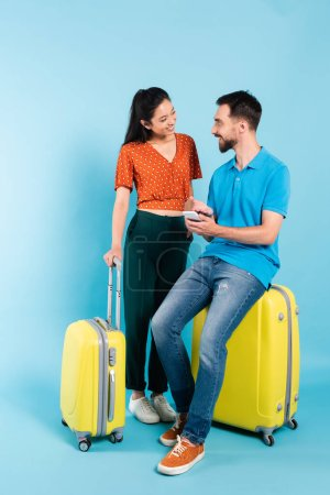 Foto de Asian woman in red blouse looking at boyfriend sitting on suitcase and pointing with hand at smartphone on blue - Imagen libre de derechos