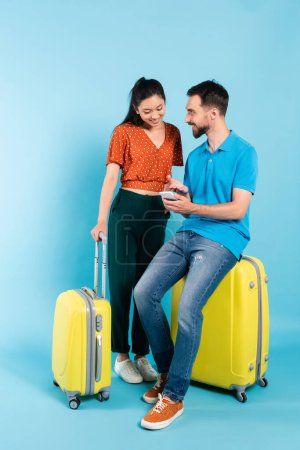 bearded man in polo t-shirt pointing with hand at smartphone while sitting on suitcase near asian girlfriend on blue