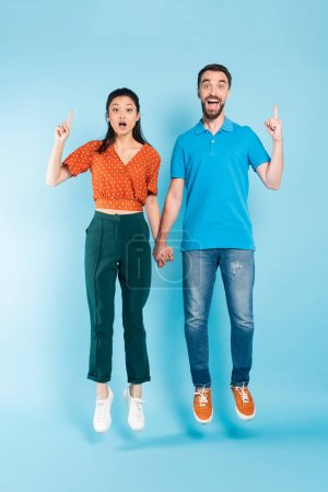 Photo for Excited asian couple holding hands and showing idea gesture while levitating on blue - Royalty Free Image
