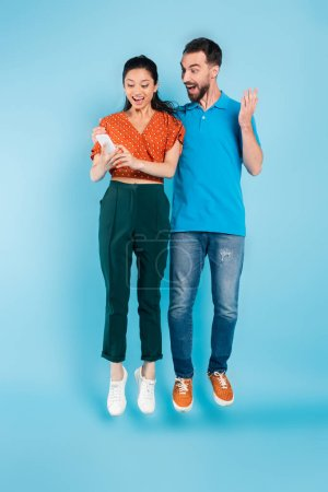 excited man touching asian woman using smartphone while levitating on blue