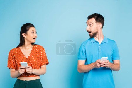 excited interracial couple looking at each other while holding smartphones on blue