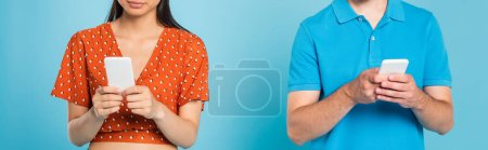 Photo pour Cropped view of woman in red blouse and man in polo t-shirt using smartphones on blue, panoramic orientation - image libre de droit