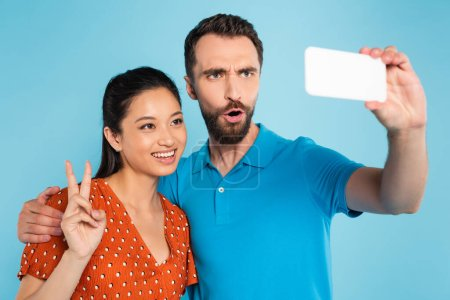 bearded man grimacing while taking selfie with asian woman showing victory gesture isolated on blue