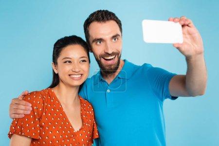 Photo pour Homme barbu en polo t-shirt prendre selfie sur smartphone avec femme asiatique en chemisier rouge isolé sur bleu - image libre de droit