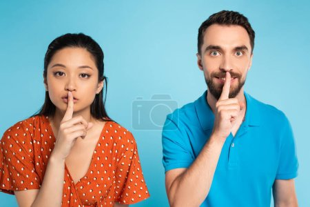 Photo pour Young asian woman in red blouse and man in polo t-shirt showing hush gesture on blue - image libre de droit