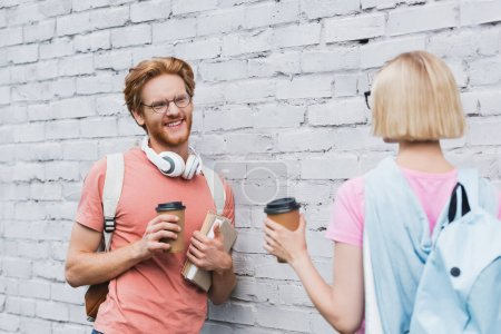 Photo for Selective focus of bearded student looking at blonde friend while holding coffee to go near brick wall - Royalty Free Image