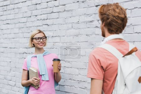 selective focus of blonde woman in glasses looking at redhead student while holding coffee to go and books near brick wall