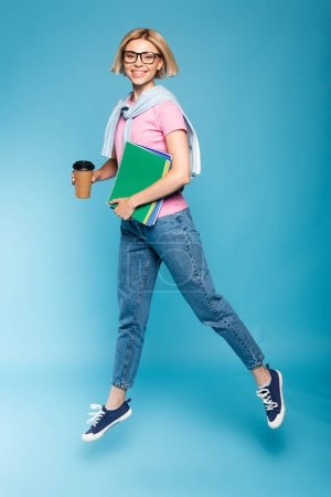 young blonde student holding paper cup and notebooks while flying on blue