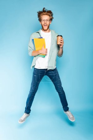 bearded student in glasses holding paper cup and notebooks while jumping on blue