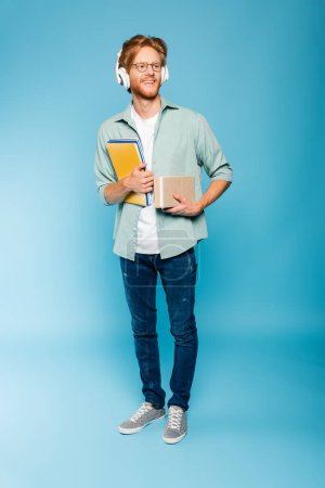 redhead and bearded student in glasses and wireless headphones holding books and notepads on blue