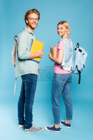 students with backpacks holding notebooks and books while standing on blue