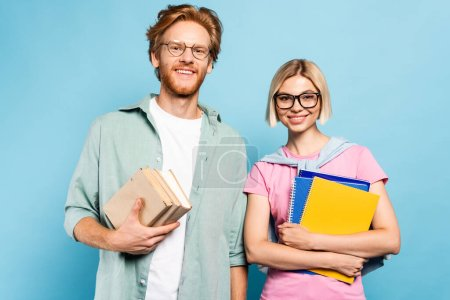 young students in glasses holding notebooks and books while standing on blue