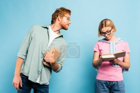 Photo pour Curieux étudiant regardant femme blonde lecture livre sur bleu - image libre de droit