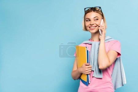 junge blonde Studentin hält Notizbücher in der Hand und spricht auf dem Smartphone auf blau