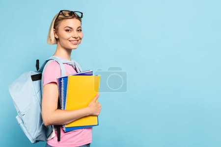 young blonde student with backpack holding notebooks on blue