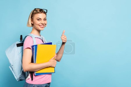 blonde student with backpack holding notebooks and showing thumb up on blue