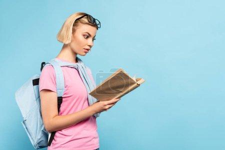 Schockierter blonder Student mit Rucksack liest Buch auf blau