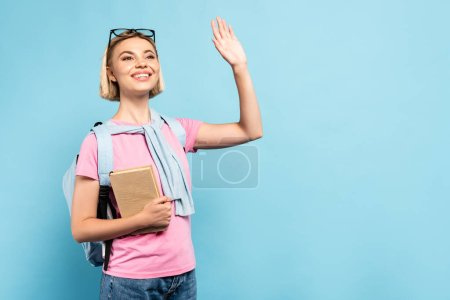 young blonde student with backpack holding book and waving hand on blue