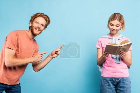 Photo pour Barbu étudiant pointant avec les doigts à blonde femme lecture livre sur bleu - image libre de droit