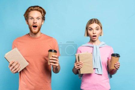 Photo pour Choqué jeunes étudiants tenant des livres et des tasses en papier sur bleu - image libre de droit