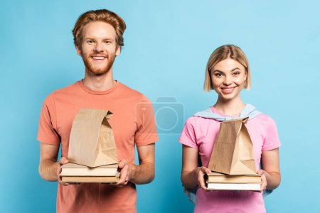 redhead and blonde students holding paper bags and books on blue