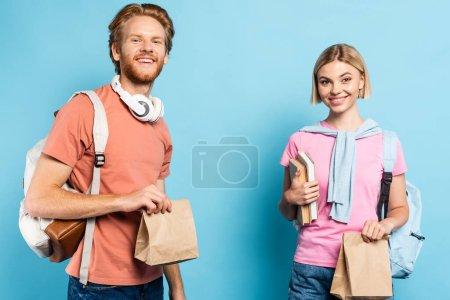 young students with backpacks holding paper bags on blue
